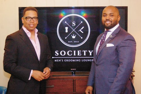 GROOMED FOR SUCCESS—Society owners K. Chase Patterson, left, and Ryan Norman pose in front of their logo shown on the HD screen in the grooming lounge's downstairs sitting room. (Photo by Rossano P. Stewart)